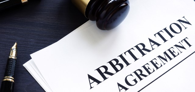 Arbitration agreement and gavel on a desk