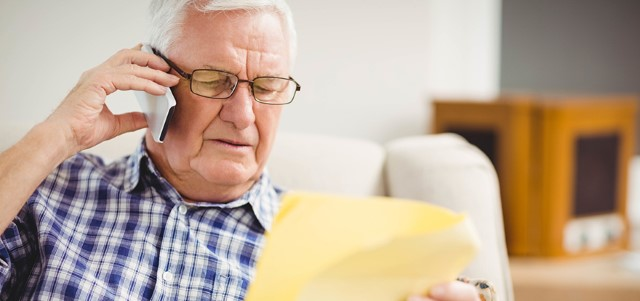 Senior man talking on mobile phone while looking at document